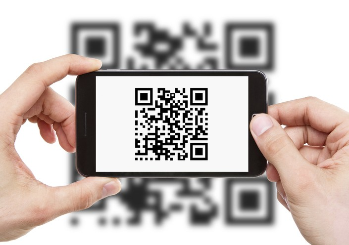 Human hands holding smart phone with qr code on it
